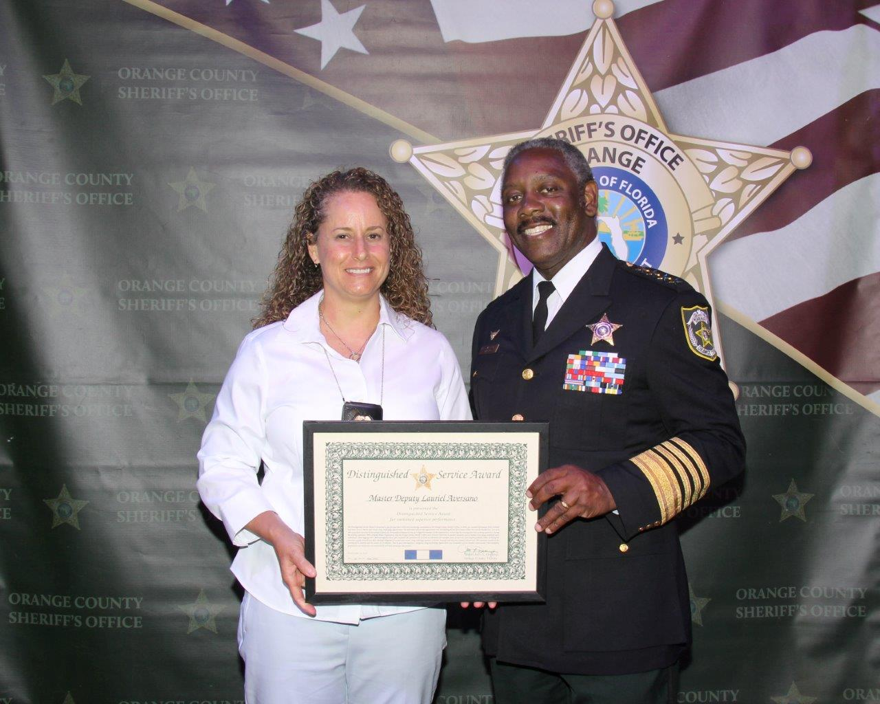 Sheriff Demings presents the Distinguished Service Award to Master Deputy Laurie Aversano