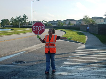 School Crossing Guard holding stop sign in street