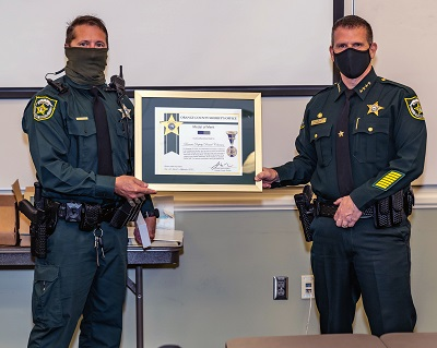 During COVID-19 our reserves have still been active protecting our community.  Here Sheriff John Mina presents the Medal of Merit for live saving to a reserve.